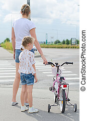 Mother and daughter with bicycle on zebra crossing.
