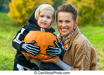 mother and daughter with carved Halloween pumpkin