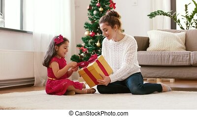 mother and daughter with christmas gift at home - holidays,...