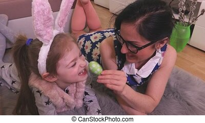 Mother and daughter with Easter eggs on the floor