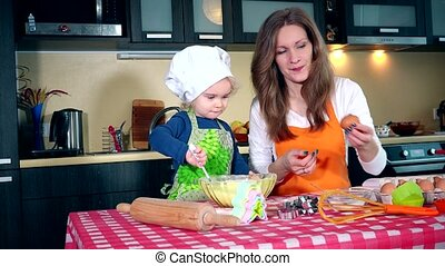 Mother and daughter with egg while cooking cake together in kitchen