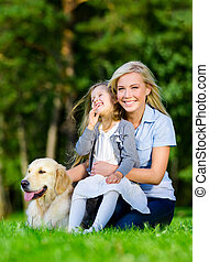 Mother and daughter with golden retriever are on the grass -...