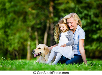 Mother and daughter with labrador are on the grass