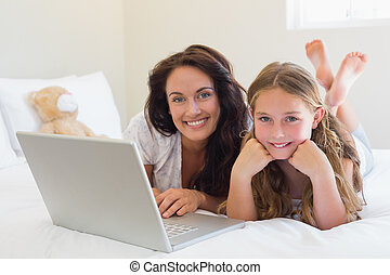 Mother and daughter with laptop in bed