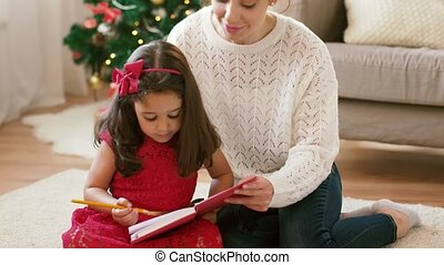 mother and daughter with notebook at christmas