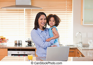 Mother and daughter with notebook in the kitchen together