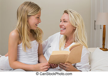 Mother and daughter with novel in bed