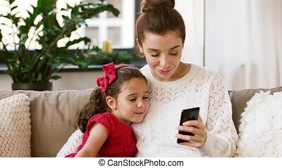 mother and daughter with smartphone at home - christmas,...