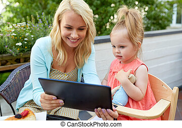 mother and daughter with tablet pc at cafe terrace