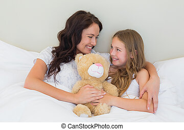 Mother and daughter with teddy bear in bed