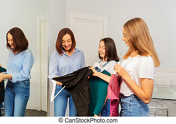 Mother and daughters choosing dresses in boutique