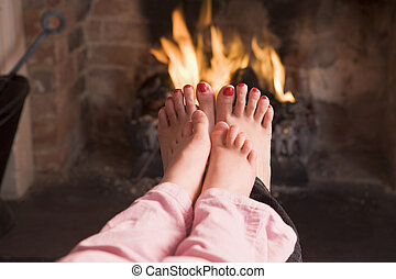 Mother and daughter\'s feet warming at a fireplace
