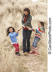 Mother And Daughters Having Fun In Sand Dunes