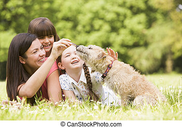 Mother and daughters in park with dog smiling