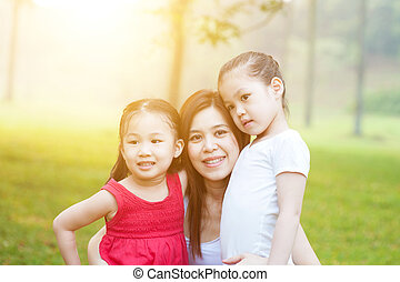 Mother and daughters in the nature.