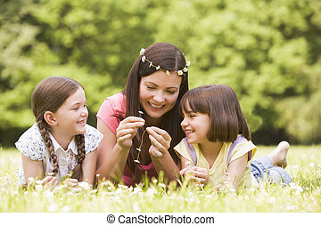 Mother and daughters lying outdoors with flowers smiling
