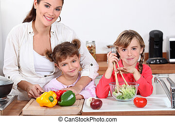 Mother and daughters making a salad.