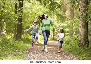 Mother and daughters skipping on path smiling
