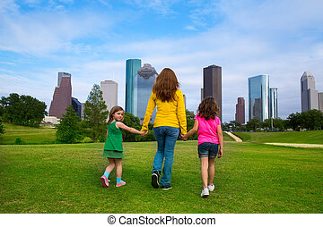 Mother and daughters walking holding hands on city skyline...