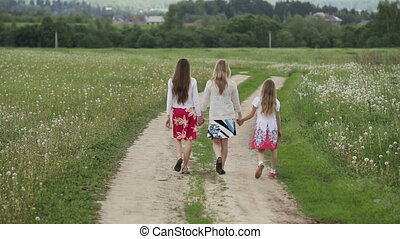 mother and daughters walking holding their hands