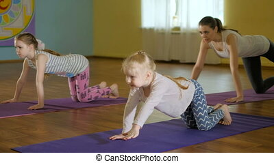 mother and daughtersr doing yoga together in a fitness studio 4k