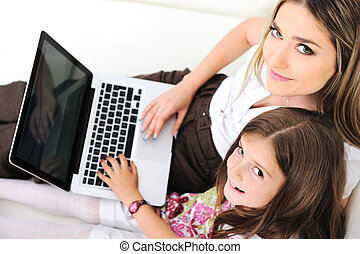Mother and daugther with laptop on sofa
