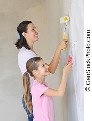 Mother and douther painting a wall with roller