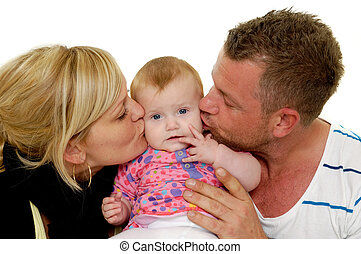 Mother and father are kissing baby