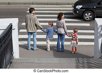 mother and father holds hand of little daughter and son and standing near crossover, behind, black car on road