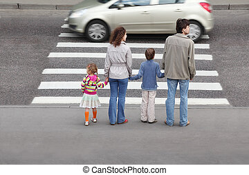 mother and father holds hand of little daughter and son and...