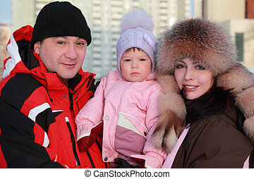 mother and father kept his little daughter, winter, warm clothing, focus on girl
