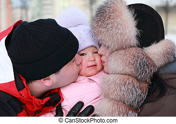 mother and father kissing his little daughter, winter, multistore building, focus on girl