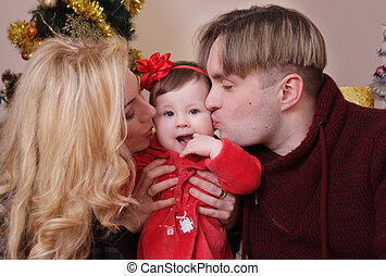 Mother and father kissing their baby girl