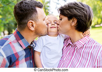 mother and father kissing their little son at park