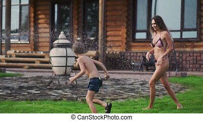 Mother and father playing with children on the lawn of the house pouring water from a hose