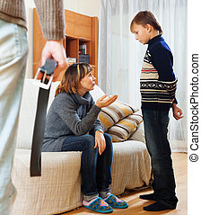 Mother and father with belt scolding teenager son at living...