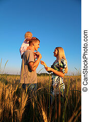 Mother and father with child on shoulders on wheat field