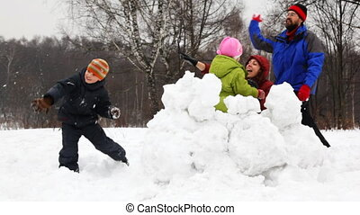 mother and father with children play snowballs behind fortress, part1