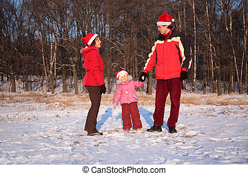 Mother and father with daughter in wood in winter