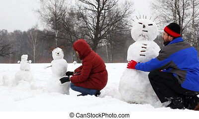 mother and father with daughter make three snowman