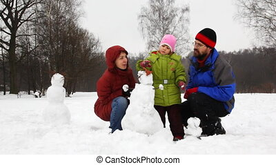 mother and father with daughter put cap on snowman