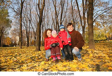 mother and father with the children in the park in autumn