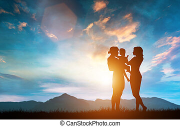 Mother and father with their child outdoors.