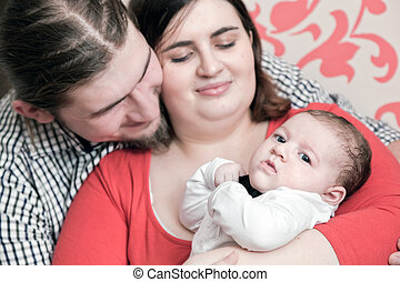 Mother and father with their young baby. Happy young family portrait.