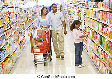 Mother and father with young daughter shopping at a grocery store.