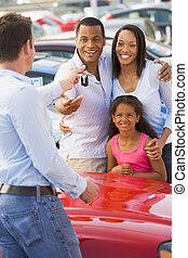 Mother and father with young daughter shopping for a new car