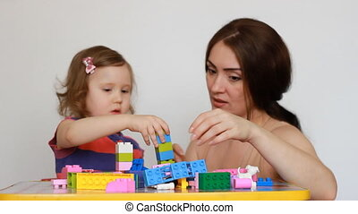 Mother and girl child busy building a constructor. Mom and...