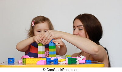 Mother and girl child busy building a constructor. - Mother...