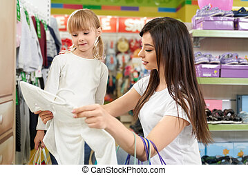 Mother and girl doing shopping in boutique with clothing.