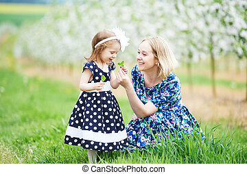 mother and girl in spring blooming garden